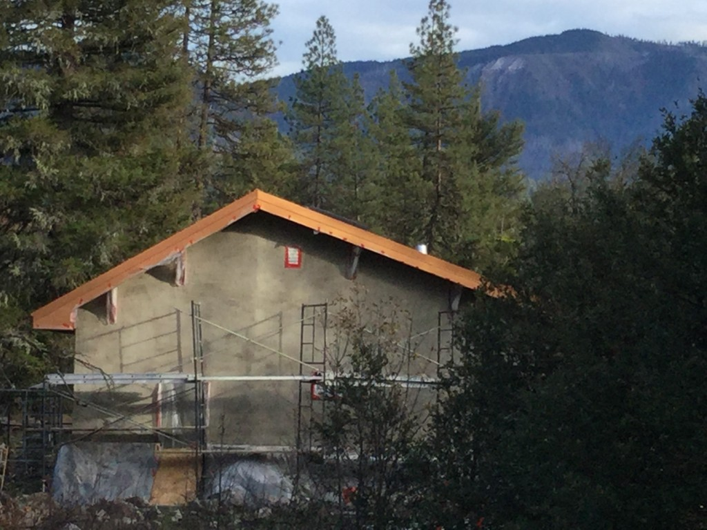Straw Hall with first coat of Natural Hydraulic Lyme plaster and copper-color steel roof flashing.